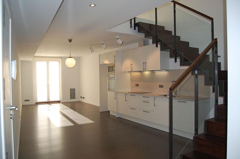 Escalera de madera y hierro cocina abierta edificio Figueres